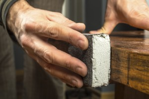 Maler schleift Holzoberfläche ab