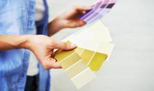 Person sucht Wandfarbe aus