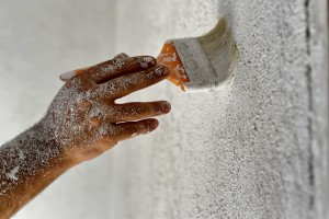 Malerhand streicht Wand